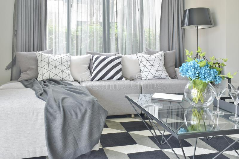 Light gray L shape sofa set with varies pattern and color pillows in living room. Light gray L shape sofa set with varies pattern and color pillows in modern stock photos