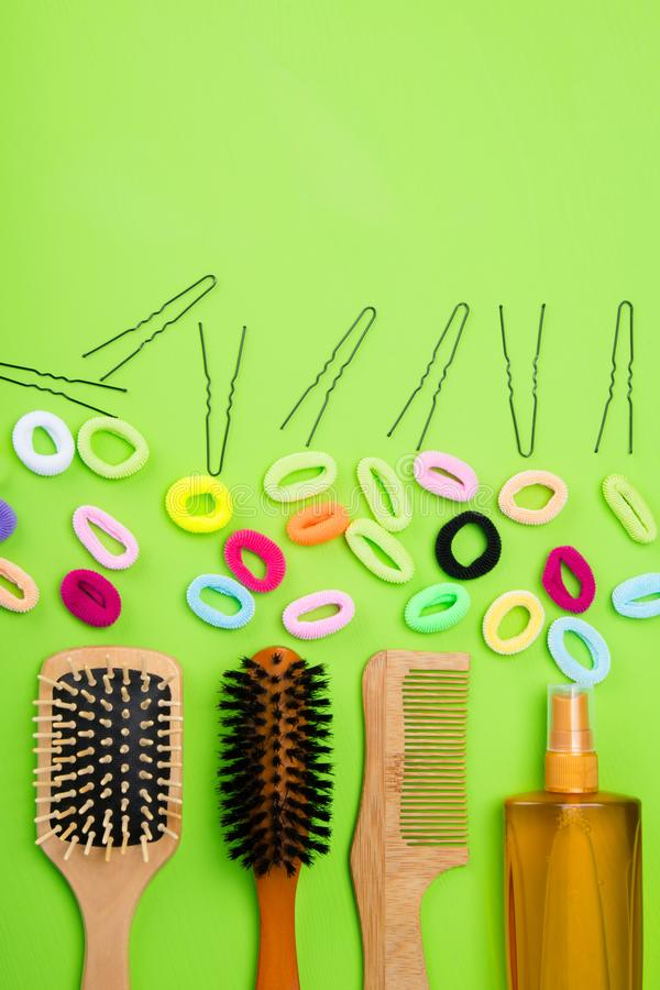 On a light green background are objects to create hairstyles. multi-colored rubber bands, black hairpins. And combs royalty free stock photography