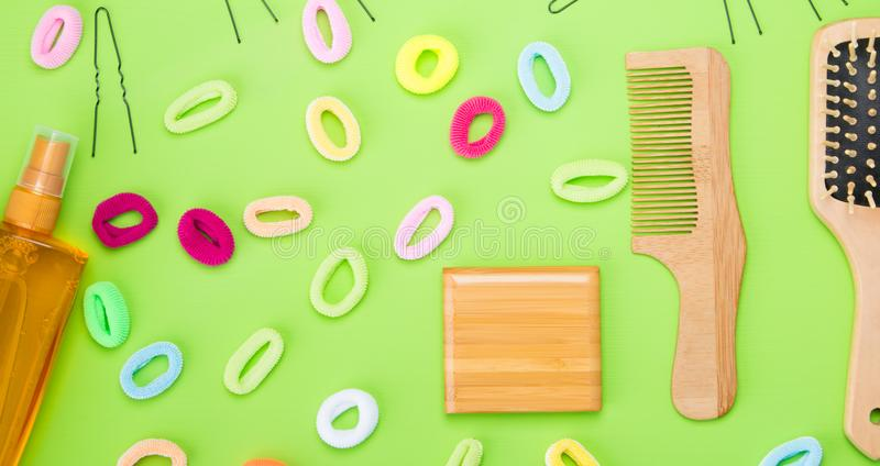 On a light green background, scattered objects to create hairstyles, gum different colors, and a comb. And a spray for styling stock photography