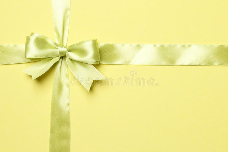 Ight green bow and ribbon isolated on yellow background royalty free stock photo