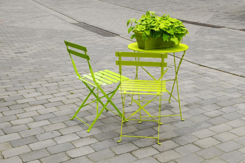 Light green garden chairs and a folding table with a green flower box on the gray cobbled marketplace, art concept, color in. The concrete desert of the urban stock photos