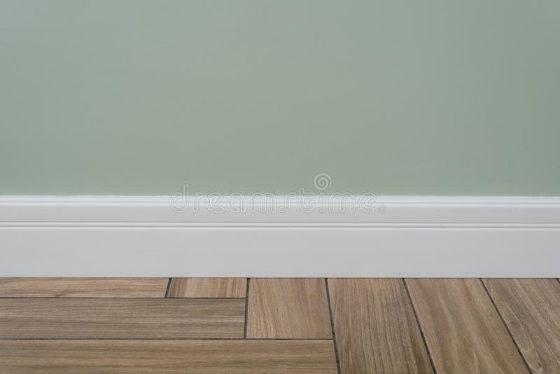 Light green matte wall, white baseboard. Interior concept. Light green matte wall, white baseboard and tiles immitating hardwood flooring royalty free stock photography
