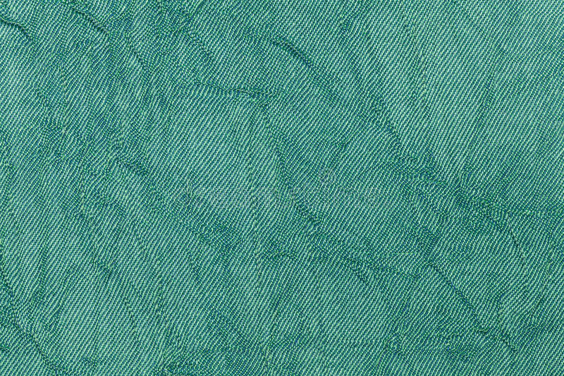 Light green pearl wavy background from a textile material. Fabric with natural texture closeup. stock image