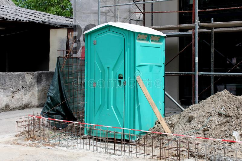 Light green portable ecological toilet left on construction site surrounded with sand and other construction material with old royalty free stock images