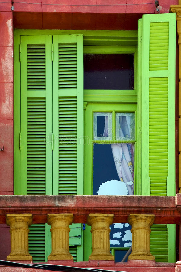 Light green wood venetian blind. And a red terrace wall in la boca buenos aires argentina stock image