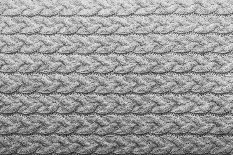 Light grey knit pattern. Light grey knit fabric background with horizontal cable pattern, wool texture in soft grey and white tones stock photo