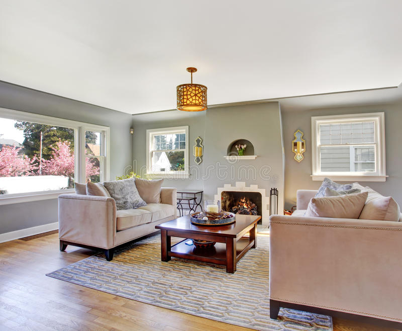 Light grey living room with white sofas and fireplace stock photography