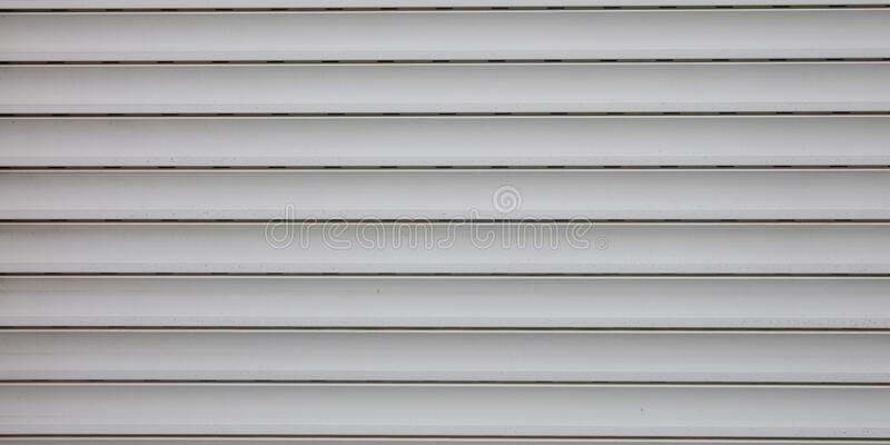 Light grey plastic texture metallic roller shutter door gray panels background. A Light grey plastic texture metallic roller shutter door gray panels background royalty free stock image
