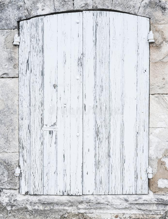 Light grey or white old shutters in limestone wall of french provence house royalty free stock photography