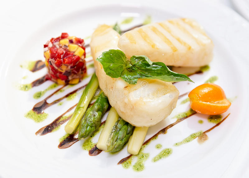 Light grilled fish with salad and asparagus stock photos