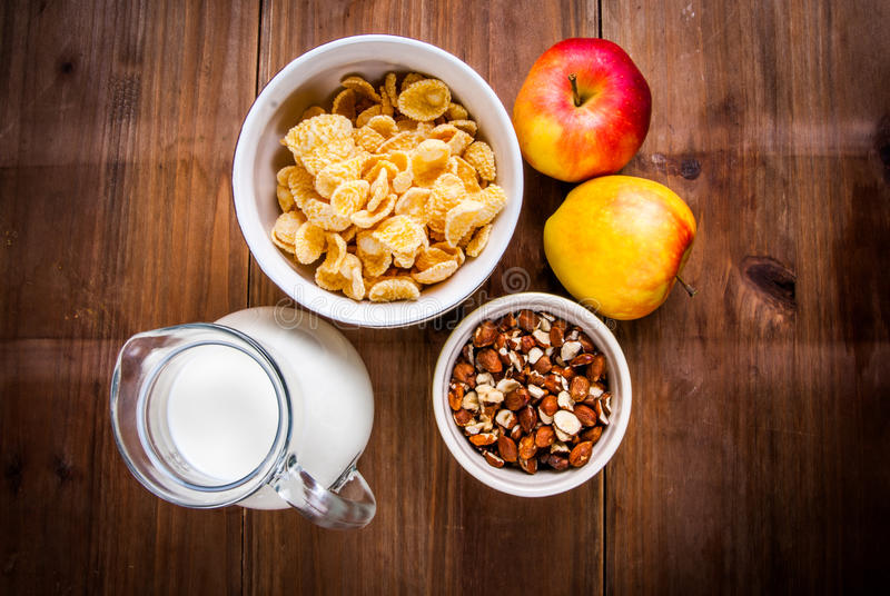 Light healthy breakfast: cornflakes, milk, apples and nuts royalty free stock photo