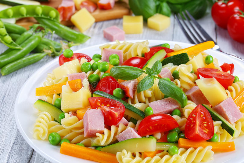 Light healthy colorful antipasto salad, close-up. Light healthy colorful antipasto salad of italian pasta fusilli with carrot and zucchini sticks, ham, cheese royalty free stock images