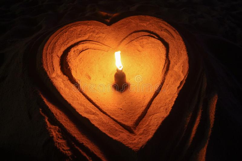 Light in heart and heart in sand stock photography
