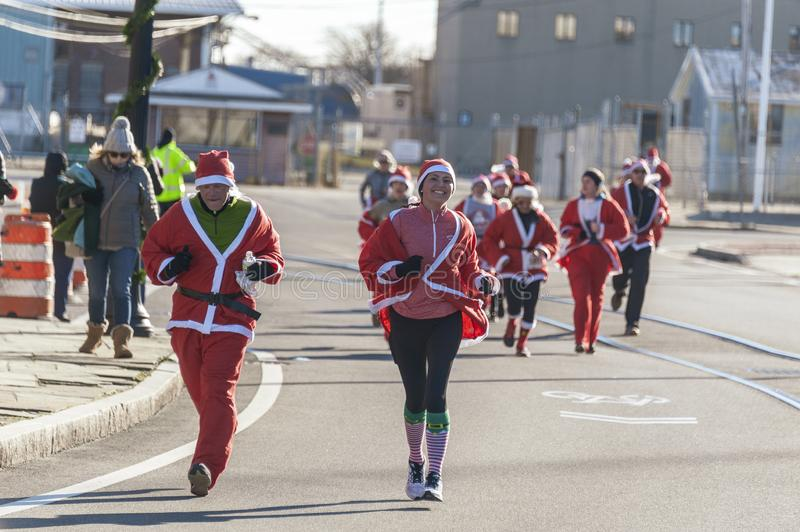 Light-hearted Santa. New Bedford, Massachusetts, USA - December 8, 2018: Santa wearing a big smile as she heads for the finish of the Santa Sightings 5K Fun Run stock images