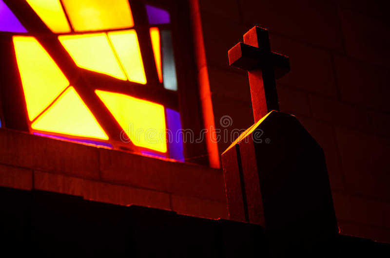 Light on the holy cross. Stained glass window casting light on the holy cross royalty free stock photography