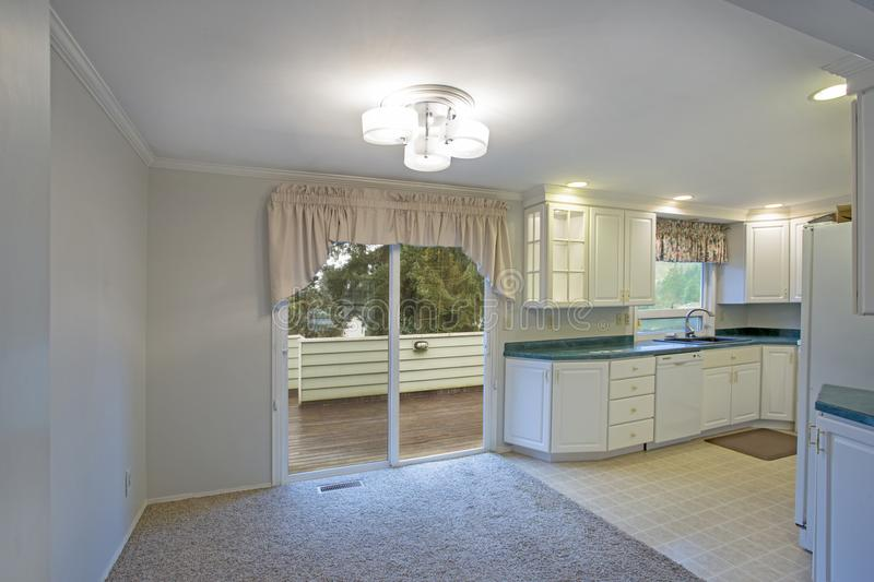 Light home interior with white kitchen cabinetry. And dining area with exit to walk out deck stock image