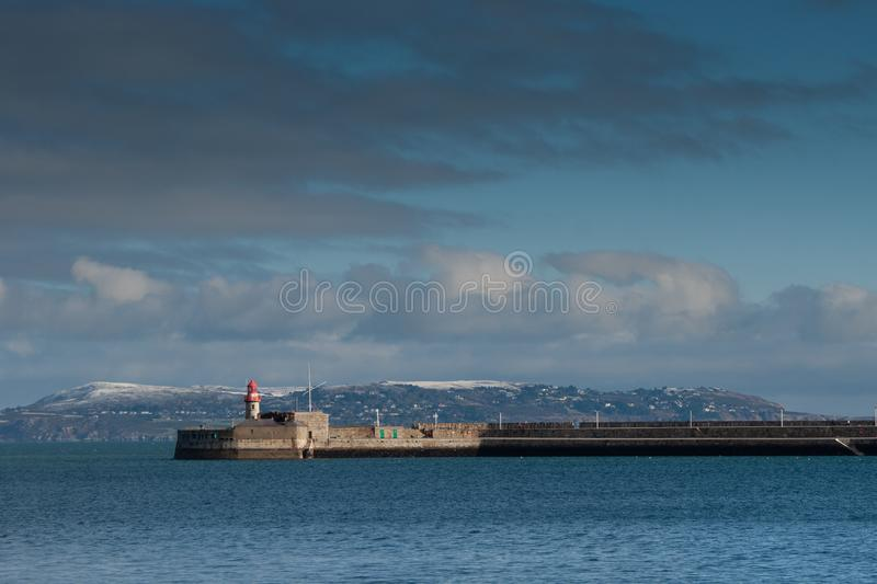 The light house in dun laoghaire harbour with hill of Howth cover by snow, Ireland stock photo