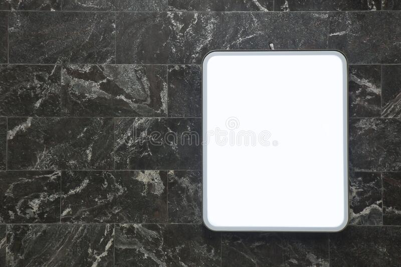 Light information panel on the wall of dark marble tiles stock image