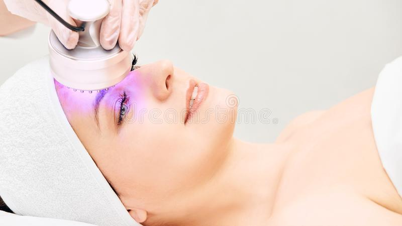 Light infrared therapy. Cosmetology head procedure. Beauty woman face. Cosmetic salon device. Facial skin rejuvenation royalty free stock photos