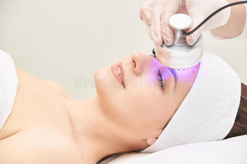 Light infrared therapy. Cosmetology head procedure. Beauty woman face. Cosmetic salon device. Facial skin rejuvenation.  royalty free stock images