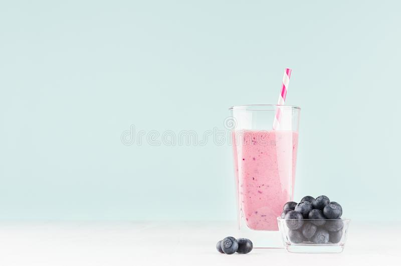 Light joyful spring milk drink with striped straw, blueberry in bowl on modern pastel mint green color background and white wood. stock image