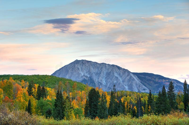 Marcellina Mountain stands between the Colorado fall colors and the calm pastel morning skies. The light just before sunrise provides pastel colors to the stock photos
