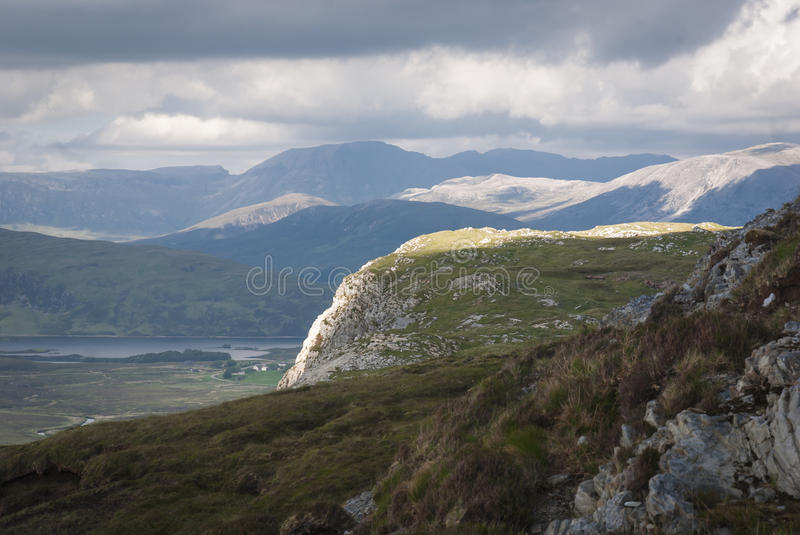Light on Knockan Crag. Sunshine lighting up the edge of Knockan Crag with Cam Loch and the Assynt mountains in the background royalty free stock photography