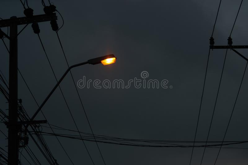 light lamp on pole with electric wires on dark night sky background stock image