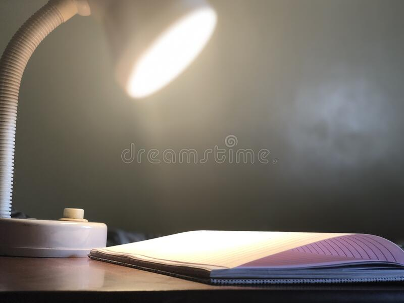 Light lamp shining on open book. Light lamp shining upon an open book royalty free stock photos