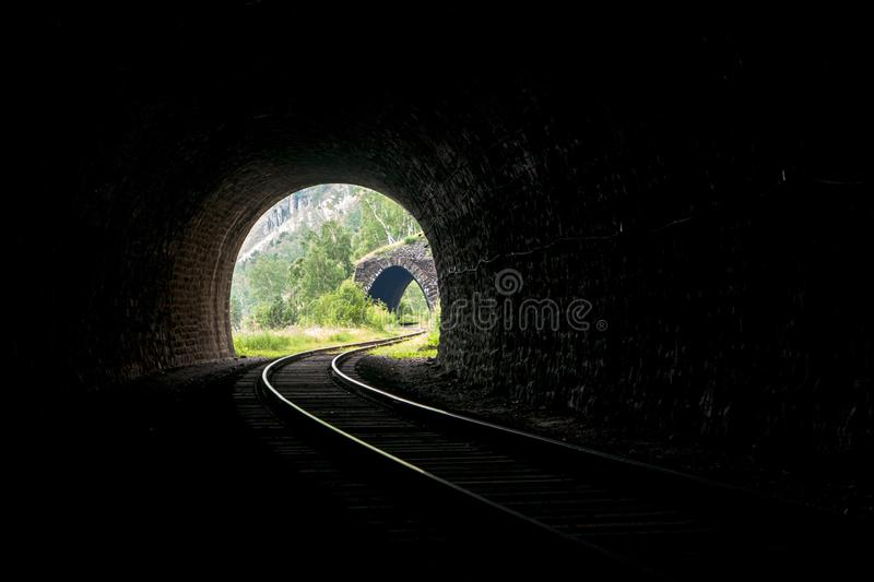 Light with a landscape at the end of a stone railway tunnel with beautifully lit rails in the mountains stock photos