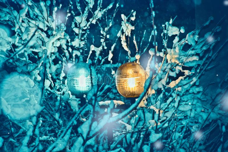 Light lantern and snow-covered trees on a cold winter night. Branches covered with snow, blue sky, and shining electric lighting pole through snowflakes in a stock image