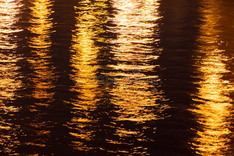Light of lanterns on the smooth surface of water at night as a background royalty free stock photo