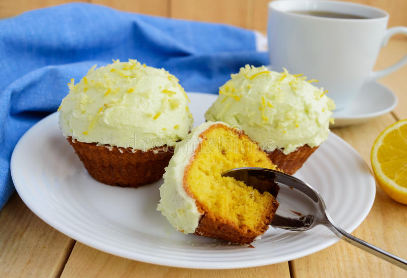 Light lemon cupcakes muffins. On wooden background and a cup of tea royalty free stock images