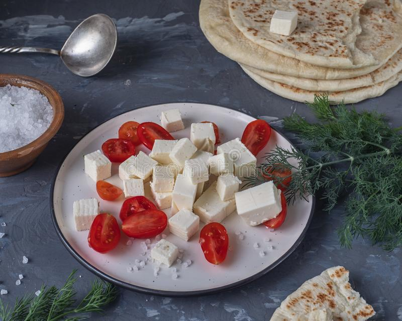 Light lunch with homemade pita, cherry tomatoes and curd cheese, dill sprigs and coarse salt in the salt shaker on a gray stock image