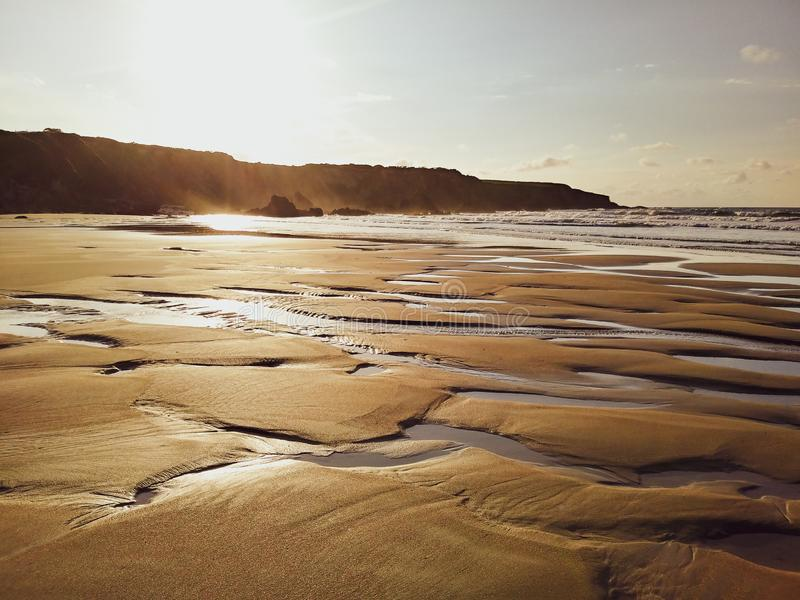 The light of a magical sunset reflected in the sand of the beach. Low tide on the beach at sunset. A magical moment with nice sweet colours. Golden sand and stock image