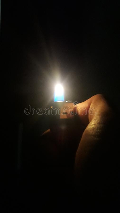 Light a match in darkness stock photography