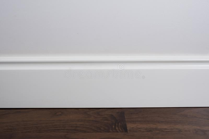 Light matte wall, white baseboard and tiles immitating hardwood flooring.  stock image