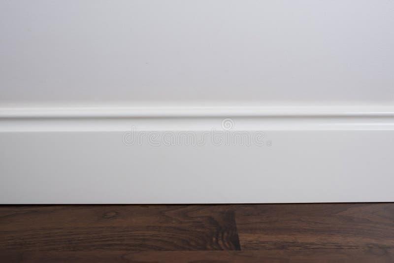 Light matte wall, white baseboard and tiles immitating hardwood flooring stock image