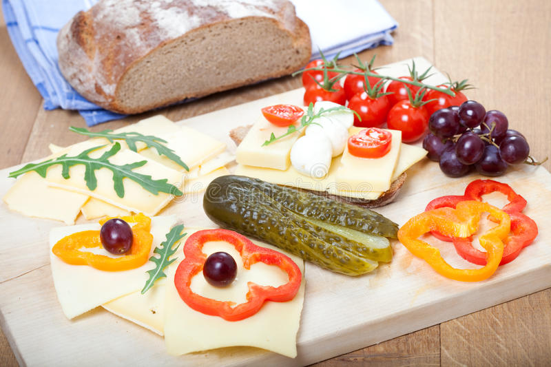 Light meal with cheese on bread, with vegetables and fruits stock photos