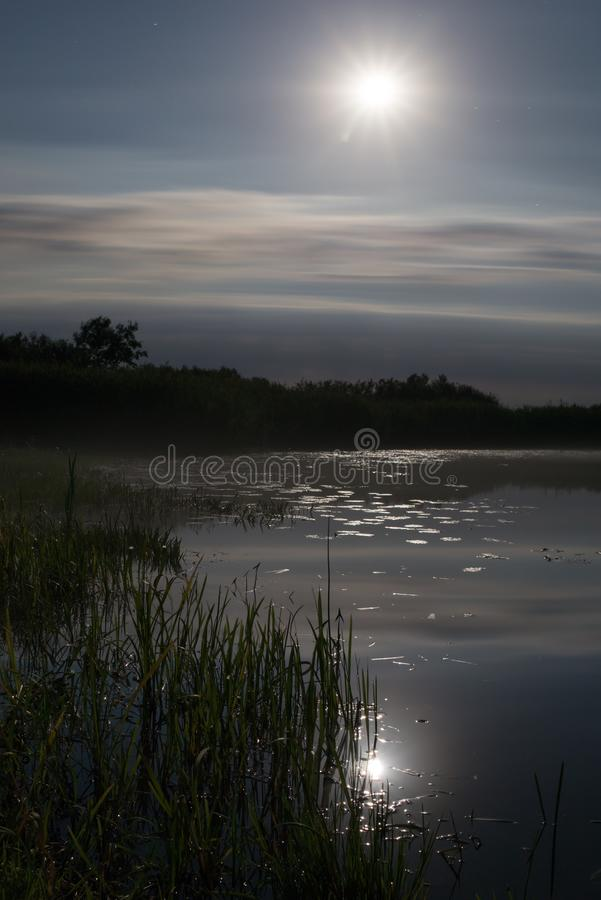 Full moon over foggy river Stochid in Volyn. Moon light at night landscape. Summer night fishing time stock photos