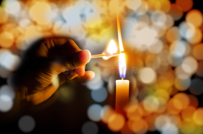 Light the night. Hand lighting candle with match stick concept of eliminating dark