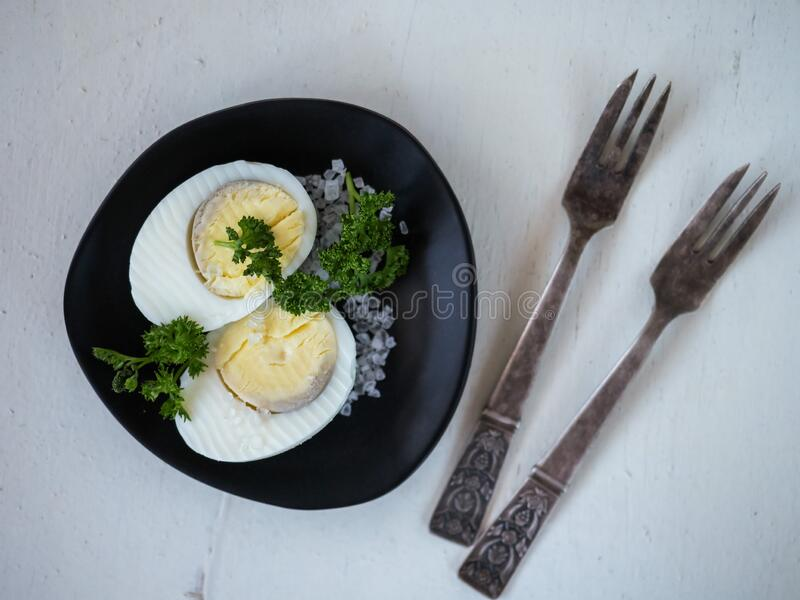 Light nutritious breakfast made of halves of an egg and sprigs of parsley with salt on a black plate. stock photography