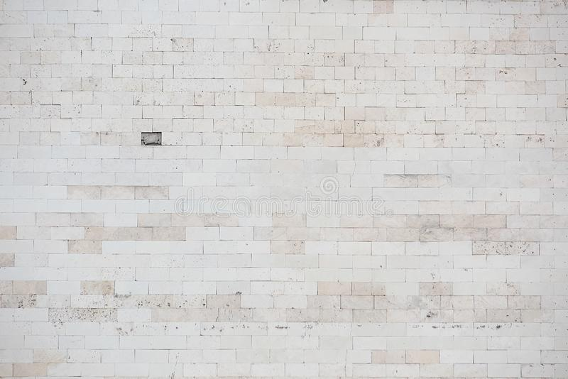 Light old wall with one fallen off tile. Texture of a light old wall with one fallen off tile, uneven, cover, background, building, surface, pattern stock photo