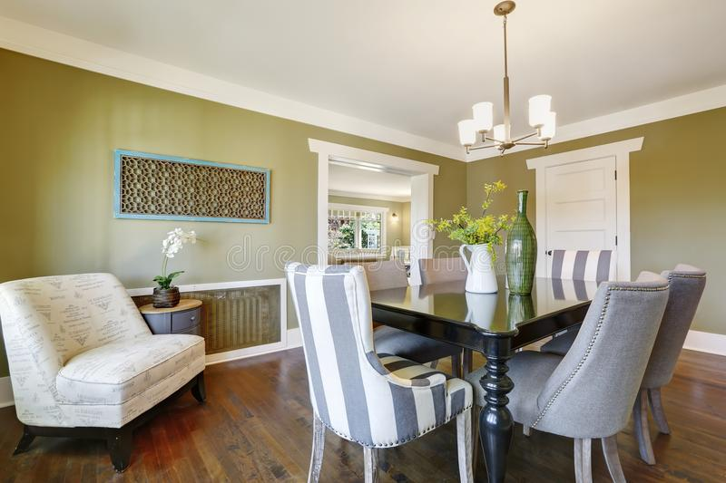 Light olive dining room features a wood carved dining table. Light olive dining room features a black dining table with carved wood legs lined with grey and royalty free stock photo