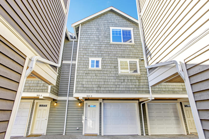 Light olive house in clapboard siding trim. Clapboard siding house in light olive color with white entrance door and driveway royalty free stock image