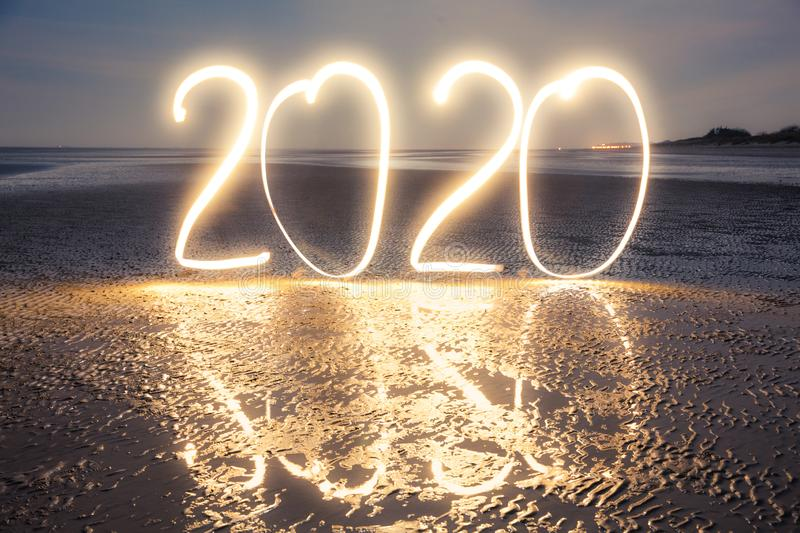 Light painting: Happy New Year 2020. Happy New Year 2020: Celebrating the new year with big glowing numbers on the beach at night stock photo
