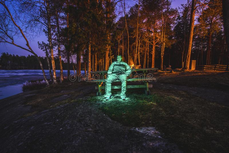 Light painting of human sitting on bench in night landscape with long exposure and glow of yellow fire light illuminated stock photography
