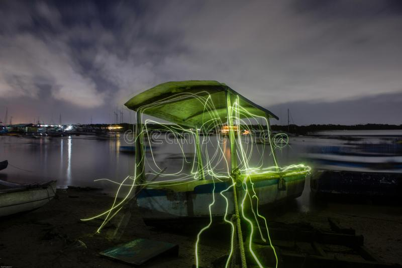 Light painting list on boat burn and bright. Landscape picture of sailors boat on the sea, using light painting on long exposure technique to make bright list royalty free stock photos
