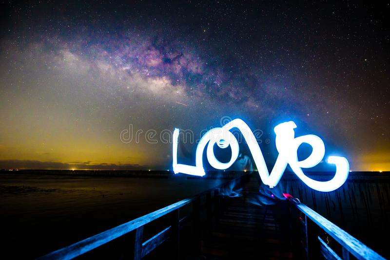 Light painting the LOVE word and milky way royalty free stock image
