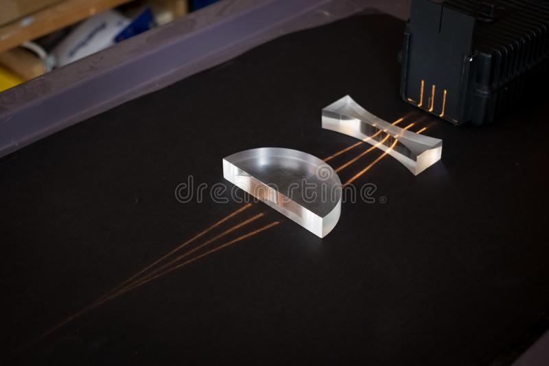 Light passing through two different kind of lenses, showing a pattern of divergent and convergent light beams. Four parallel light beams travel through two royalty free stock photos